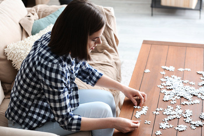 young woman working jigsaw puzzle at home - social distancing