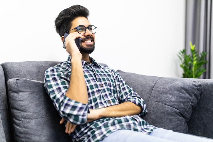 young man smiling and talking on phone while at home on couch - loneliness - quarantine