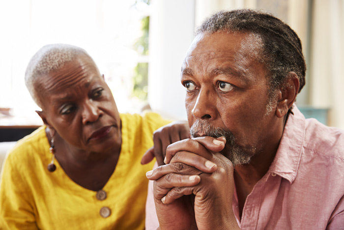 senior African American couple - woman comforting man - older adults