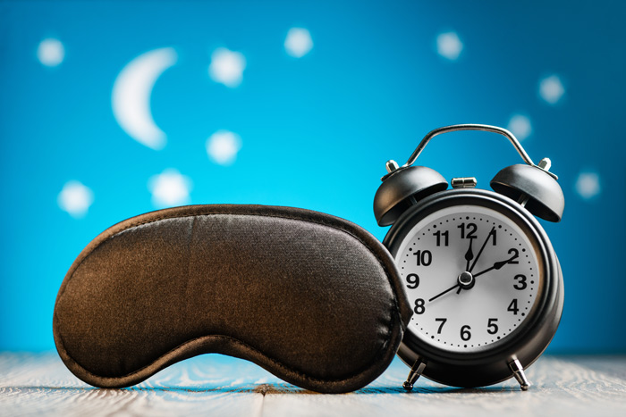 black sleeping mask next to old fashioned alarm clock - sleep