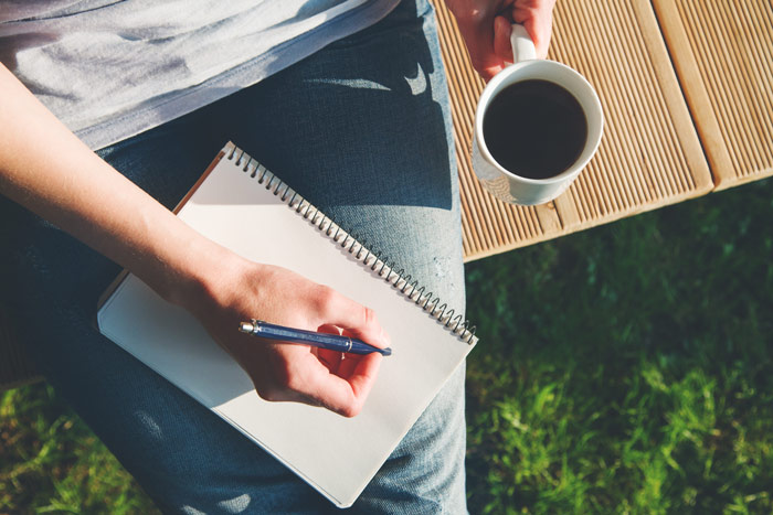 person holding mug of coffee and writing in journal while sitting outdoors - journaling