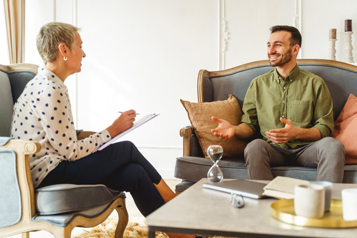 smiling man in therapy session with smiling female counselor - cognitive behavioral therapy