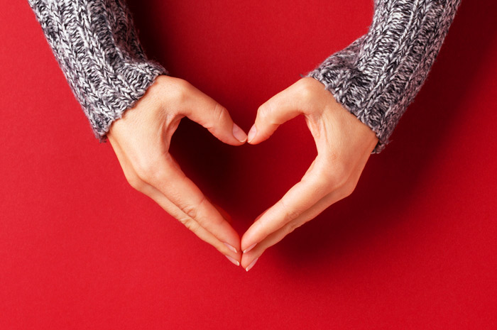 woman's hand forming the shape of a heart against a bright red background - values