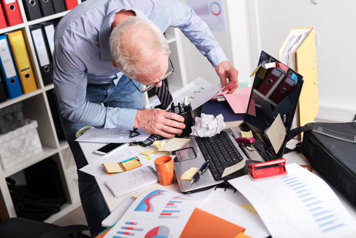 senior man in office rummaging through desk looking for something - decluttering