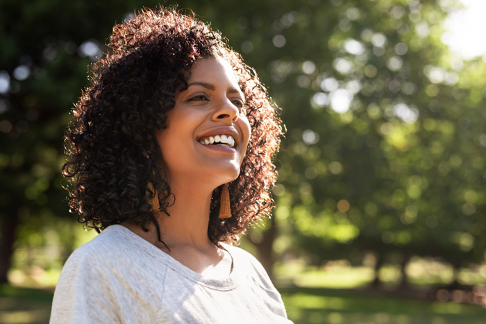 beautiful smiling woman of mixed ethnicity outdoors in a park - physical and mental health