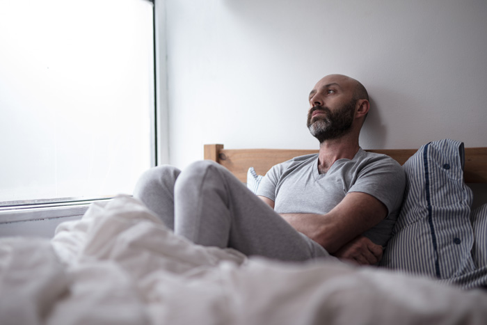 man sitting up in bed looking very depressed - dysthymia