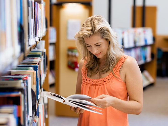 pretty woman browsing through a book in a bookstore - mental health memoirs