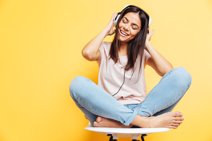 pretty young woman with dark hair sitting in a chair listening to music on headphones - music